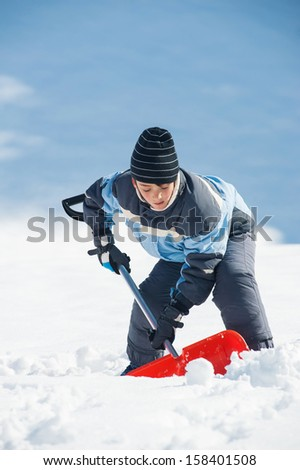 Young kid with shovel outdoors. - stock photo