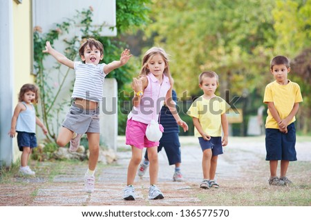 Young kids playing together outdoors. - stock photo