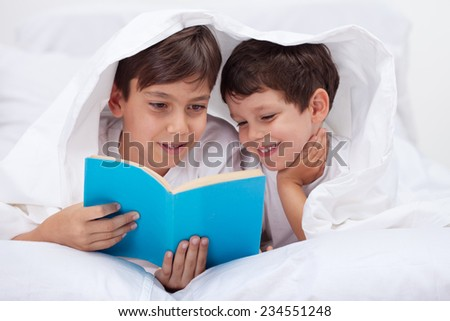 Young kids reading under the blanket - enjoying the story - stock photo