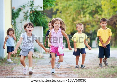 Young kids running together outdoors. - stock photo
