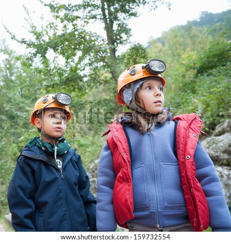 Young kids wearing helmet for cave exploration.  - stock photo