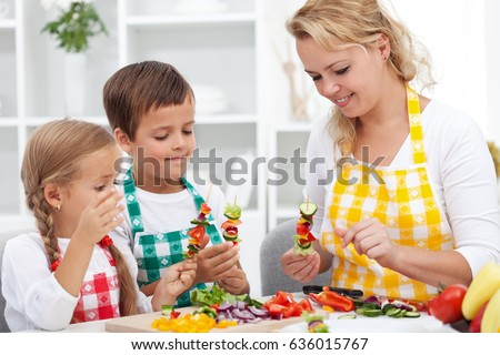 Young kids with their mother in the kitchen preparing a vegetables snack - healthy eating concept