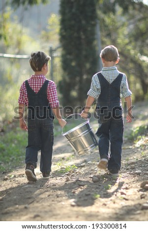Young Kids Working on the Farm  With a Pail