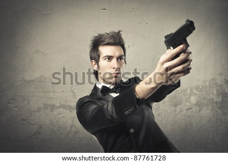 Young killer pointing a gun - stock photo