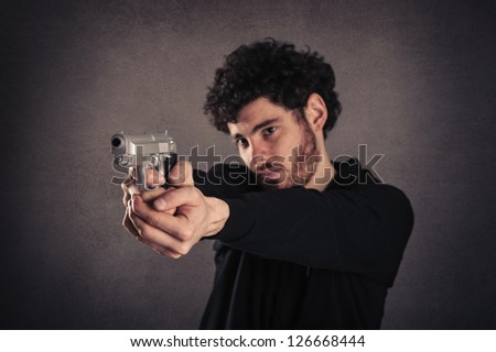 Young killer pointing a gun over grunge background. - stock photo