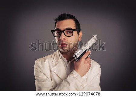 Young killer with gun portrait over dark background. - stock photo