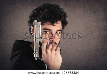 Young killer with gun portrait over grunge background. - stock photo