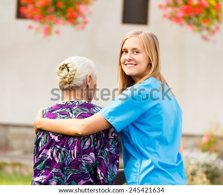 Young kind doctor helping old lady on a walk in the garden. - stock photo