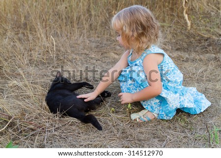 Young kind girl plays with a black cat. - stock photo