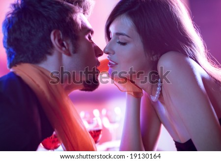 Young kissing amorous couple at celebration - stock photo