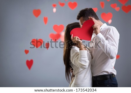 Young kissing couple with heart - stock photo