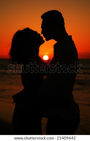 Young kissing pair  on a sunset - stock photo