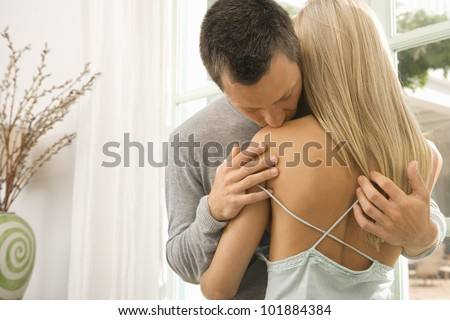 Young kissing woman's shoulder near a large window. - stock photo