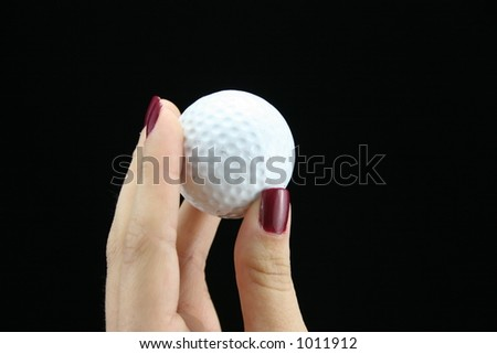 Young ladies hand holding golf ball.