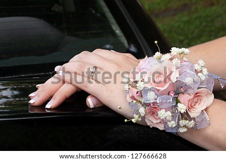 Young ladies hands with a pink rose wrist corsage - stock photo