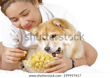 Young lady and a pet dog enjoying a bowl of popcorn.