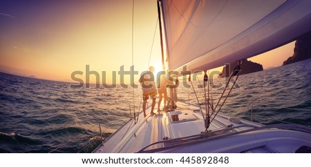 Young lady and man working with sail and rope on the sailing boat - stock photo