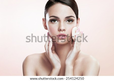 Young lady applying blusher on her face with powder puff, skin care concept / photoset of attractive brunette girl on beige background   - stock photo