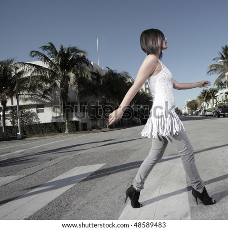 Young lady crossing the street - stock photo