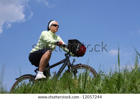 Young lady cycling, blue sky background