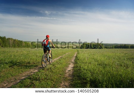 Young lady cycling on a rural road in a meadow