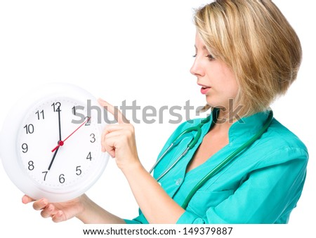 Young lady doctor is holding clock showing seven, isolated over white