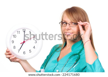 Young lady doctor is holding clock showing seven, isolated over white - stock photo