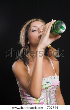 Young lady drinking from a beer bottle - very high resolution