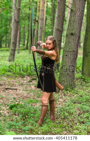 Young lady Elf with a long bow in the wild forest