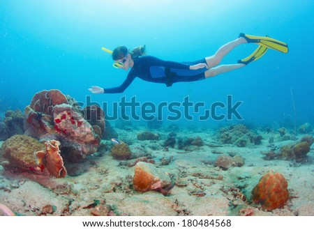 Young lady finning in the blue tropical sea over coral reef
