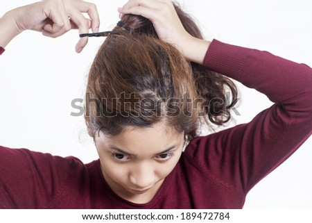 Young lady fixing a messy frizzy hair.