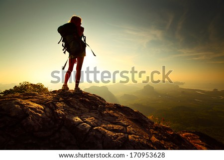 Young lady hiker standing with backpack on top of a mountain and enjoying sunrise - stock photo