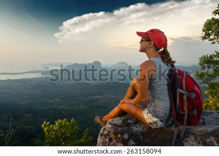 Young lady hiker with backpack sitting on the rock on top of the mountain and enjoying valley view - stock photo