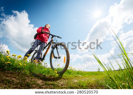 Young lady hiker with bicycle standing on a green summer meadow - stock photo