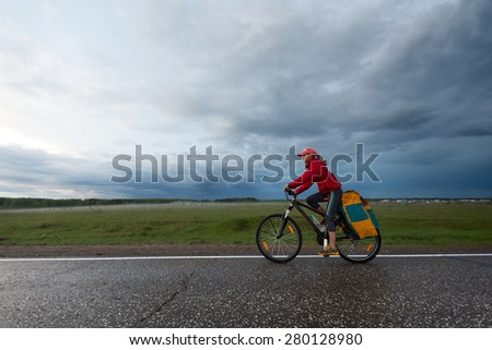 Young lady hiker with loaded bicycle riding on the wet asphalt road - stock photo