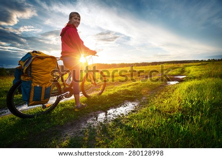 Young lady hiker with loaded bicycle standing on a wet rural road in the meadow - stock photo