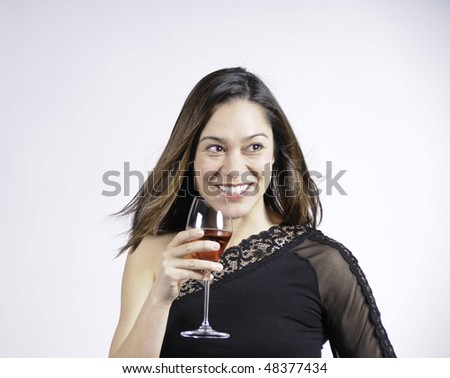 Young lady holding a glass of wine and a big smile. She is of mixed ethnicity. - stock photo