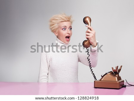 young lady holding and looking at a handset of a retro phone with a shocked face - stock photo