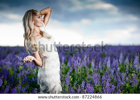 Young lady in a lavender field - shallow DOF, focus on face - stock photo