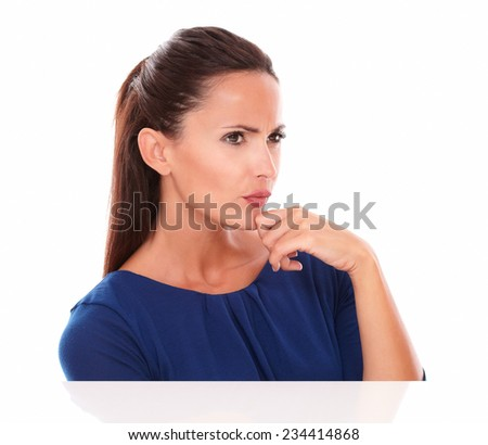 Young lady in blue blouse looking to her left while touching chin in white background - copyspace - stock photo