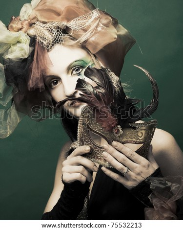 Young lady in carnival costume with mask in her hand,s