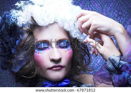 Young lady in exotic little hat and with creative make-up.