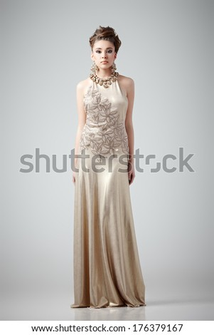 Young lady in fashionable dress posing on gray background