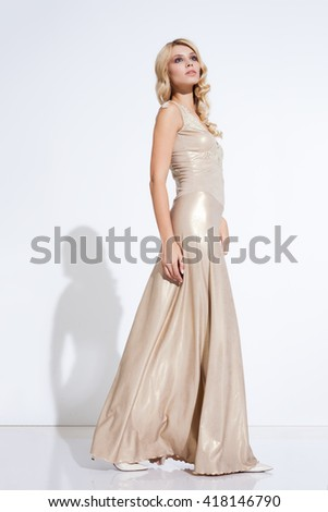 Young lady in fashionable dress posing on white background