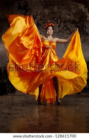 Young lady in flying silk dress on grunge background