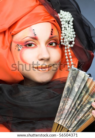 Young lady in orange turban with fan