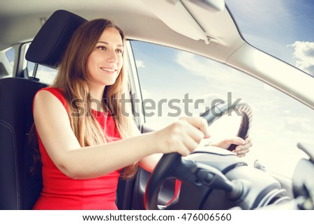 Young lady in red dress driving a car. Driving school background
