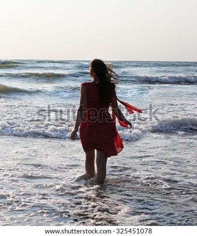 Young lady in red entering the sea - stock photo