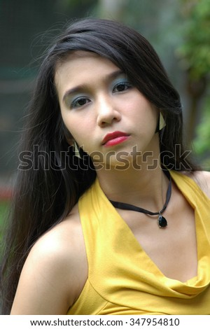 Young lady in serious mood while looking at the camera lens. Tight close ups