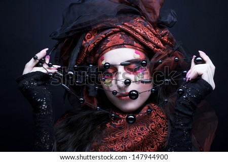 Young lady in turkish style in black and red silk and with beads - stock photo